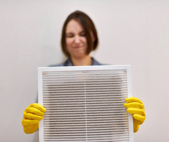 woman cleans air conditioning filter